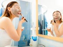Mulher que aplica a máscara do facial da lama imagem de stock