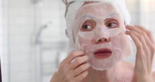 Mulher que aplica a máscara em sua cara que olha no espelho vídeos de arquivo