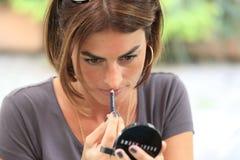 Mulher que aplica o batom Fotografia de Stock Royalty Free