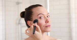 Mulher que aplica o cosmético com uma escova grande video estoque