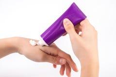 Mulher que aplica o creme da mão na palma da beleza do tubo roxo Imagem de Stock Royalty Free