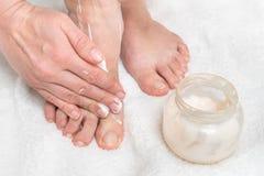 Mulher que aplica o creme do creme hidratante em seus pés fotos de stock