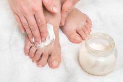 Mulher que aplica o creme do creme hidratante em seus pés imagens de stock
