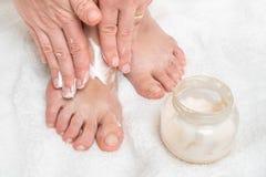 Mulher que aplica o creme do creme hidratante em seus pés fotos de stock royalty free