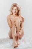 Mulher que aplica o creme do moisturizer Fotografia de Stock Royalty Free