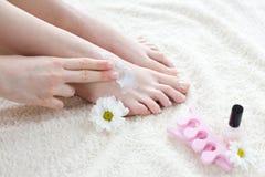 Mulher que aplica o creme em seus pés Fotos de Stock Royalty Free