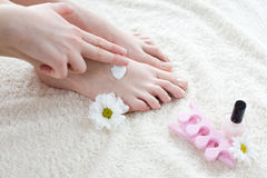 Mulher que aplica o creme em seus pés Imagens de Stock Royalty Free
