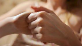 Mulher que aplica o creme hidratando em suas mãos Conceito do tratamento de mãos e do tratamento de mãos dos termas Pregos da bel video estoque