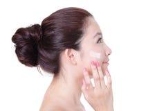 Mulher que aplica o creme na face no perfil Fotografia de Stock
