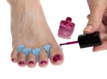 Mulher que aplica o lustrador de prego cor-de-rosa Fotografia de Stock Royalty Free