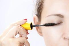 Mulher que aplica o mascara nas pestanas Fotografia de Stock Royalty Free