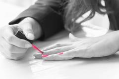 Mulher que aplica o verniz para as unhas cor-de-rosa, conceito do prego da pintura Fotos de Stock Royalty Free
