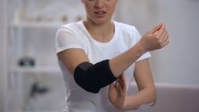 A mulher que aplica a ortose acolchoada cotovelo, sente a dor após ferimento do esporte, ortopedia filme