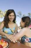 Mulher que aplica a protecção solar na filha Fotografia de Stock