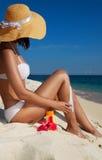 Mulher que aplica a protecção solar na praia imagem de stock