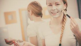 Mulher que aplica-se com m?scara da lama da argila da escova a sua cara imagem de stock