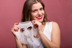 Mulher que aplica uma máscara do tecido Foto de Stock
