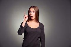 Mulher que aponta acima e que olha a câmera Imagens de Stock Royalty Free