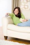 Mulher que aponta com a televisão de controle remoto Fotos de Stock Royalty Free