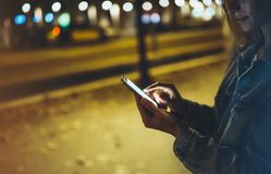 Mulher que aponta o dedo no smartphone da tela na luz do bokeh da iluminação do fundo na cidade atmosférica da noite, moderno que fotografia de stock royalty free
