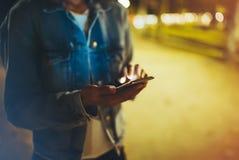 Mulher que aponta o dedo no smartphone da tela na luz do bokeh da iluminação do fundo na cidade atmosférica da noite, moderno que fotos de stock