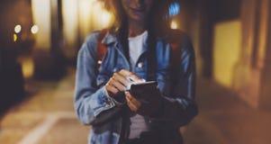 Mulher que aponta o dedo no smartphone da tela vazia na luz do bokeh do fundo na cidade atmosférica da noite, moderno do blogger  foto de stock