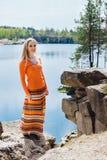 Mulher que aprecia a água azul do lago no penhasco alto no verão Fotos de Stock