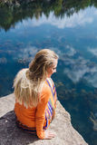 Mulher que aprecia a água azul do lago no penhasco alto no verão Imagens de Stock Royalty Free