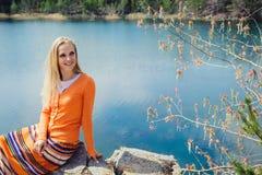 Mulher que aprecia a água azul do lago no penhasco alto no verão Imagem de Stock Royalty Free