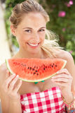 Mulher que aprecia a fatia de melão de água Fotos de Stock Royalty Free