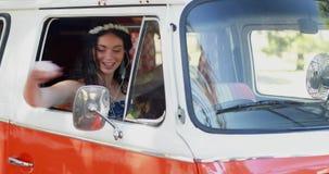 Mulher que aprecia a música ao sentar-se na camionete de campista 4k video estoque