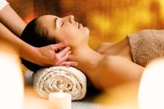 Mulher que aprecia a massagem aromática do óleo na luz de vela fotografia de stock
