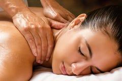 Mulher que aprecia a massagem do ombro nos termas fotos de stock royalty free