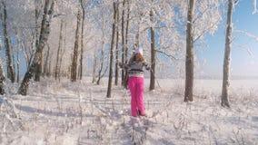Mulher que aprecia a neve do inverno que joga fora a neve e a posição sob a queda de neve vídeos de arquivo