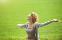 Mulher que aprecia o ar livre com a propagação dos braços aberta Fotos de Stock Royalty Free
