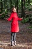 Mulher que aprecia o calor da luz solar do inverno em uma floresta Fotografia de Stock Royalty Free