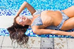 Mulher que aprecia o sunbath na borda da associação em um dia ensolarado Vocação do verão foto de stock royalty free