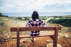 Mulher que aprecia a opinião do mar que senta-se em um banco no vale bonito Imagem de Stock