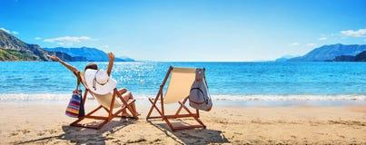 Mulher que aprecia tomar sol na praia imagem de stock