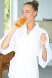 Mulher que aprecia um vidro do suco de laranja fotos de stock