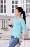 Mulher que aprecia a videira vermelha na cozinha Foto de Stock
