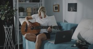 Mulher que aprende jogar a guitarra video estoque