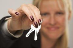 Mulher que apresenta chaves Fotografia de Stock