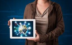 Mulher que apresenta o globo da terra 3d na tabuleta moderna Fotos de Stock