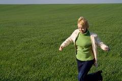 Mulher que apressa-se no campo verde Fotografia de Stock Royalty Free