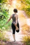 Mulher que aquece-se antes de movimentar-se, exercício exterior imagens de stock royalty free