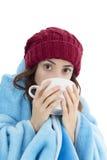Mulher que aquece-se sob uma cobertura e com um copo do chá Fotografia de Stock Royalty Free