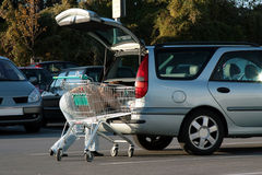 Mulher que armazena a compra no carro Fotografia de Stock Royalty Free