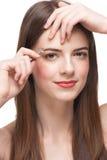 Mulher que arranca suas sobrancelhas Imagens de Stock