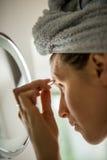 Mulher que arranca suas sobrancelhas no espelho Imagem de Stock